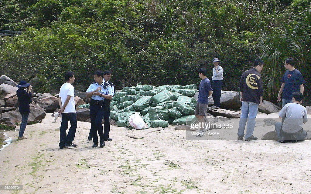STORY 'HONGKONG-CHINA-CRIME-ENVIRONMENT-ANIMALS-SMUGGLING' This photo taken 19 April 2005 shows police guarding boxes of endangered smuggled pangolins found on a beach in the remote area of Hong Kong's New Territories. The police raid that found the pangolins revealed the shipment of 2,000 of the scaly anteaters confirmed what environmentalists see as further evidence that Hong Kong, with its proximity to mainland China, has become a centre for the smuggling of rare species to China.
