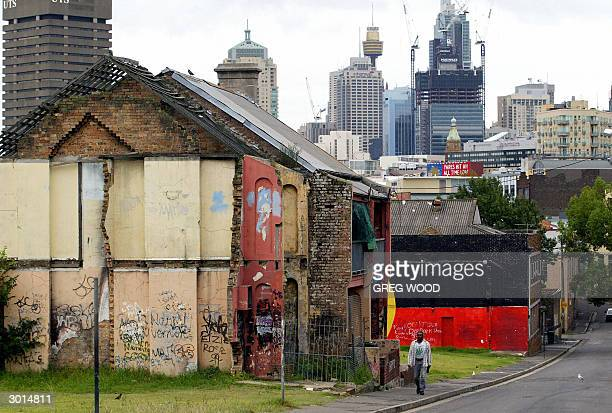 This photo taken 24 February 2004 shows an Aboriginal man walking through the controversial housing area known as 'The Block' in the inner Sydney...