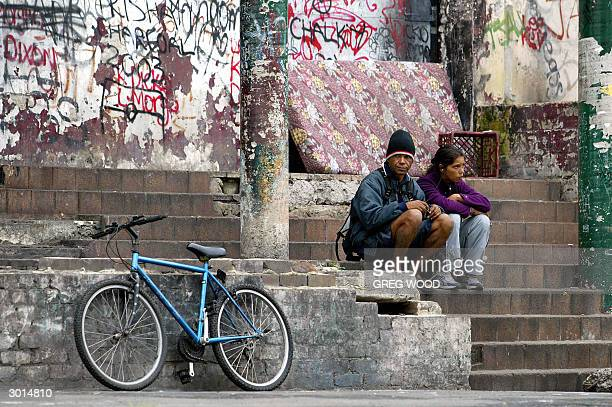 This photo taken 24 February 2004 shows two Aborigines sitting on the steps of a building in the controversial housing area known as 'The Block' in...