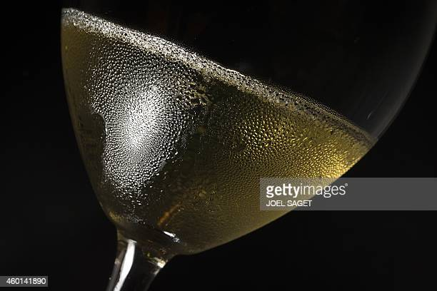 This photo taken at the 'Grand Testing' winemaking event on November 28 2014 in Paris shows a glass of brut nature or 'zerodosage' champagne made...