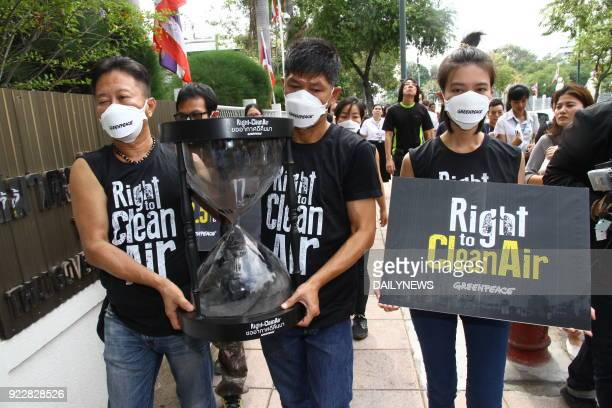 This photo taken by Thailand's Dailynews on February 22 2018 shows members of environment action group Greenpeace delivering an hourglass filled with...