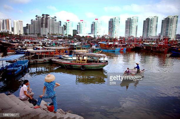 This photo taken February 6, 2012 shows Chinese fishermen docking their boats at the harbour in Haikou, south China's Hainan province. As China's...