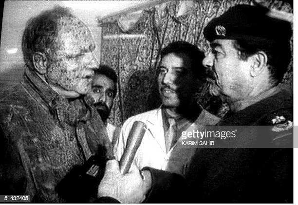 This photo taken from Iraqi television 17 January 1993 shows Iraqi President Saddam Hussein visiting a man reported to be an injured German...