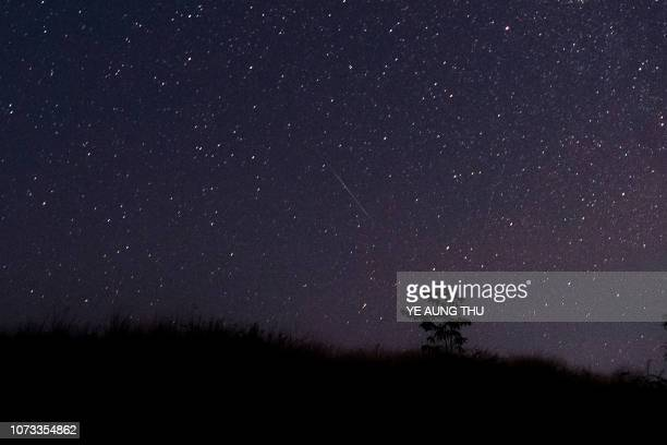 This photo taken late December 14 2018 with a long time exposure shows a meteor streaking through the night sky over Myanmar during the Geminid...