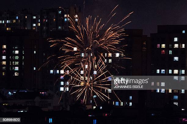 This photo taken late on February 7 2016 shows fireworks illuminating buildings of the Chinese border town of Dandong opposite to the North Korean...