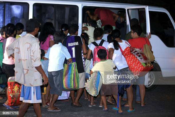 This photo taken late on January 22 2018 shows residents carrying their belongings loading into a small bus during a forced evacuation in the town of...