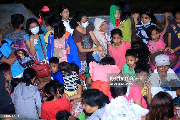 This photo taken late on January 22 2018 shows residents carrying their belongings gathered in the back of a truck during a forced evacuation in the...
