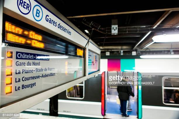 This photo taken late on March 8 2016 shows a commuter entering a train of the RER B line at the ChateletLes Halles station in Paris France was...