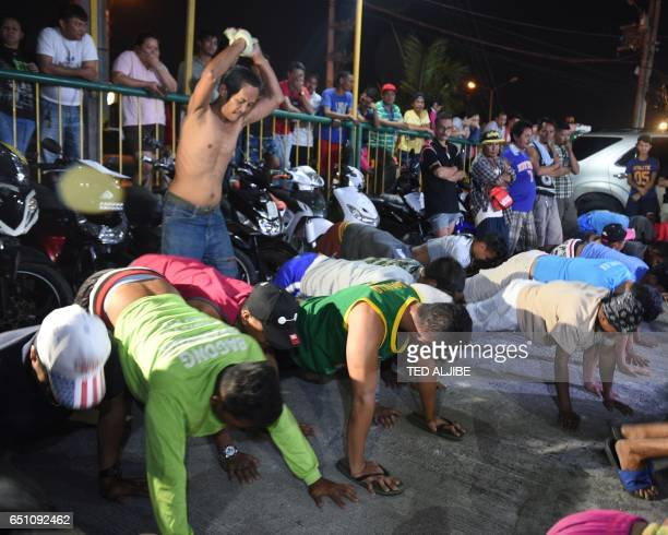This photo taken March 9 2017 shows detained bewildered drunks and shirtless men doing 60 pushups as punishement during the police's operation called...