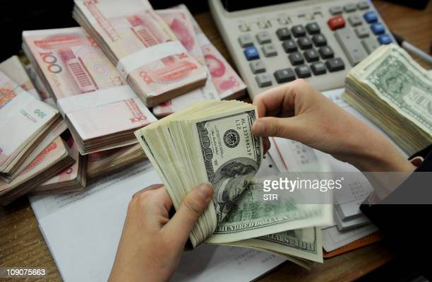 This photo taken n January 16 2011 shows a bank teller counting stacks of US dollars and Chinese 100yuan notes at a bank in Hefei east China's Anhui...