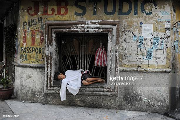 This photo taken November 10, 2015 shows a homeless boy sleeping in a condemned building window in Manila. The Philippines has swept 20,000 homeless...