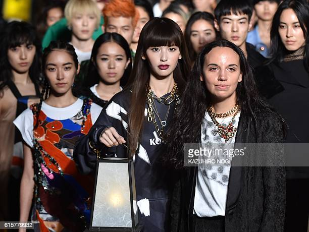 This photo taken October 19 2016 shows designer Christelle Kocher posing with models at the end of her KOCHE AW16 and SS17 mix collection show...