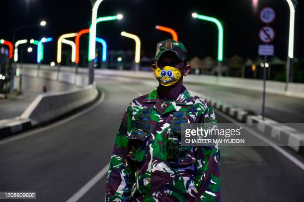 This photo taken on April 1, 2020 shows a soldier, wearing a face mask depicting popular cartoon character Spongebob Squarepants, keeping watch on a...