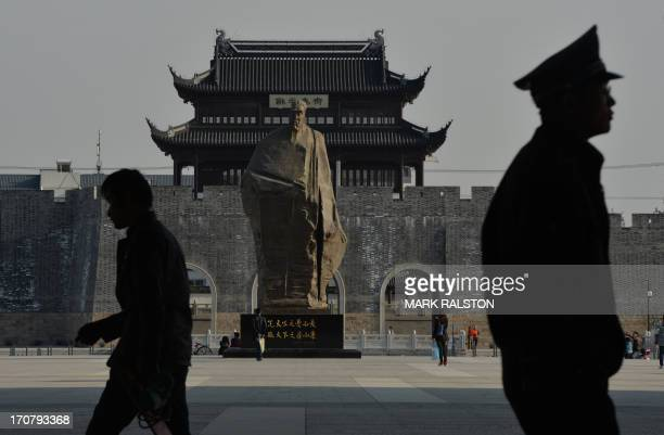 This photo taken on April 11 2013 shows a policeman walking past a statue of historic Chinese politician named Fan Zhongyan who was famous for the...