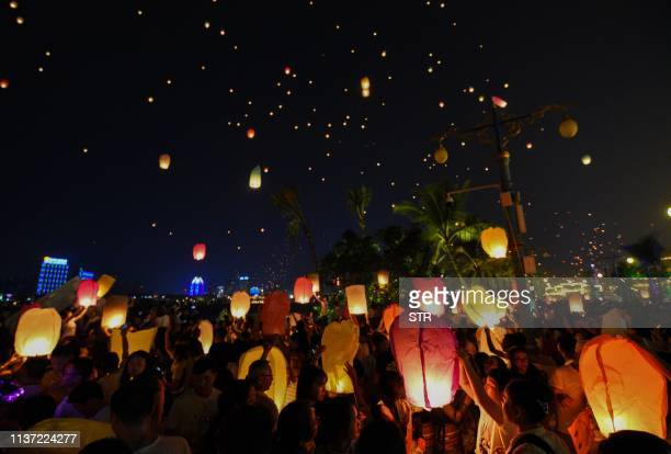 This photo taken on April 13 2019 shows people releasing sky lanterns to celebrate the annual Songkran or Thai New Year in Jinghong in China's...