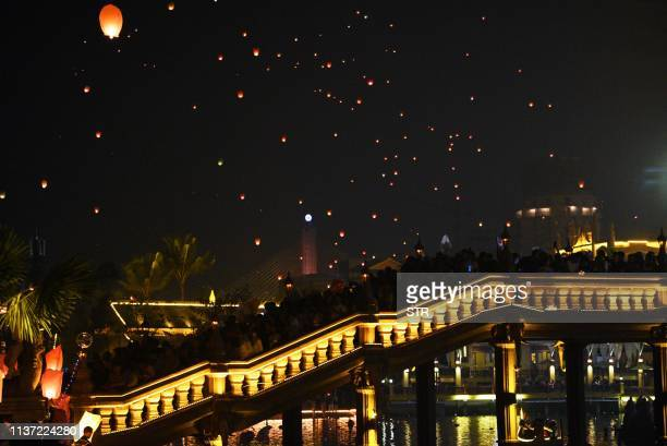 This photo taken on April 13 2019 shows sky lanterns drifting up into the air as people celebrate the annual Songkran or Thai New Year in Jinghong in...