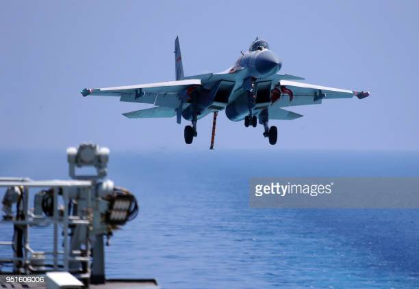 This photo taken on April 14, 2018 shows a J15 fighter jet preparing to land on China's sole operational aircraft carrier, the Liaoning, during a...