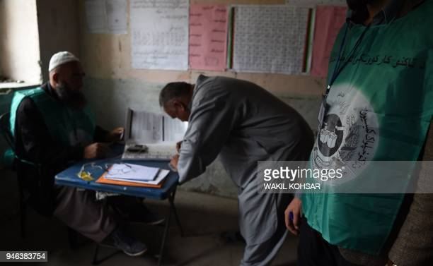 This photo taken on April 14 2018 shows Afghan employees of the Independent Election Commission registering a resident at a voter registration center...