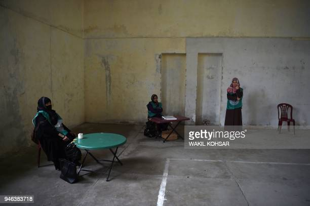 This photo taken on April 14 2018 shows Afghan women working with the Independent Election Commission waiting to register residents at a voter...