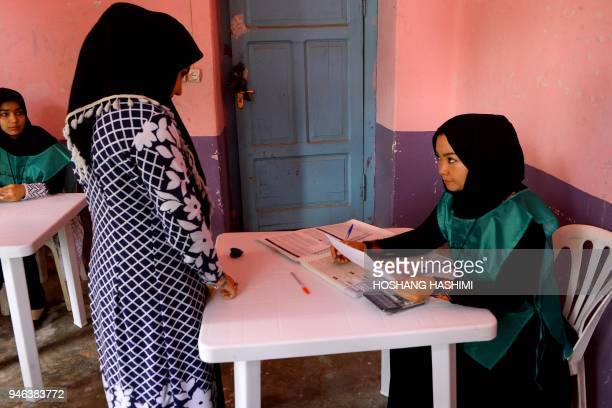 This photo taken on April 14 2018 shows an Afghan employee of the Independent Election Commission registering a resident at a voter registration...