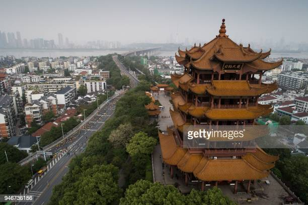 This photo taken on April 15, 2018 shows participants running past the Yellow Crane Tower as they compete in the Wuhan Marathon in Wuhan in China's...