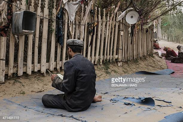 This photo taken on April 16, 2015 shows a Uighur man praying at the tomb of Imam Asim in Hotan, in China's western Xinjiang region. Chinese...