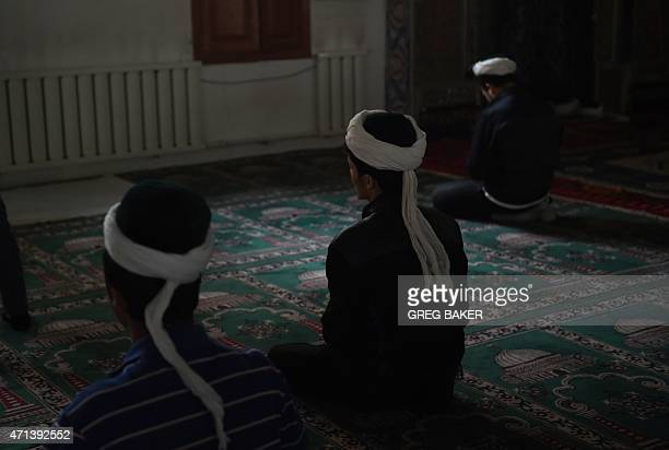 This photo taken on April 16 2015 shows Uighur men praying in a mosque in Hotan in China's western Xinjiang regionChinese authorities have restricted...