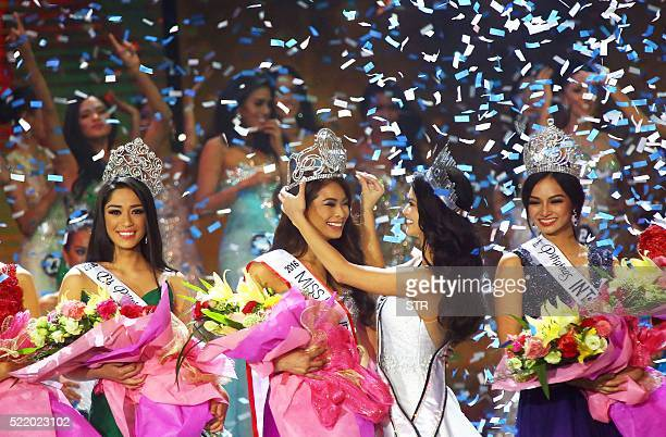 This photo taken on April 17 2016 shows Miss Universe 2015 Pia Wurtzbach giving the Miss Philippines crown to her successor Maxine Medina during the...