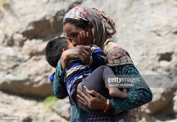This photo taken on April 18 2018 shows a Kashmiri Muslim Bakarwal nomad holding her son at a temporary camp near Udhampur some 72km north of Jammu...
