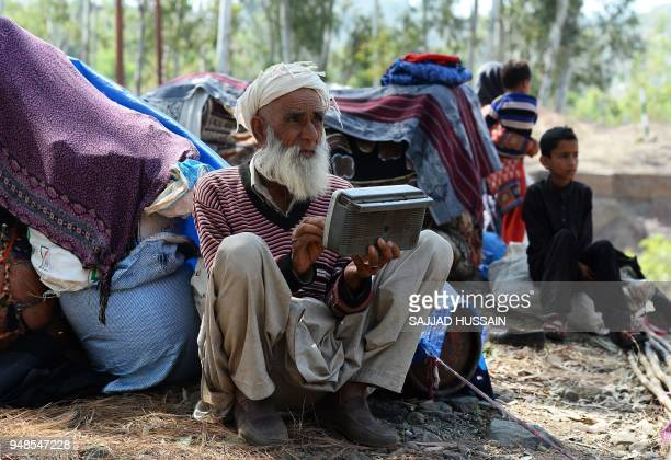 TOPSHOT This photo taken on April 18 2018 shows a Kashmiri Muslim Bakarwal nomad listening to the radio at a temporary camp near Udhampur some 72km...