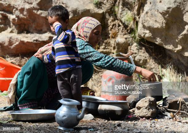 This photo taken on April 18 2018 shows a Kashmiri Muslim Bakarwal nomad preparing food at a temporary camp near Udhampur some 72km north of Jammu in...