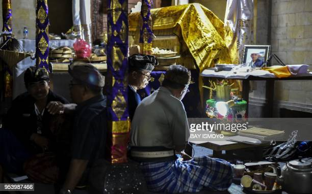 This photo taken on April 18, 2018 shows Balinese family members chanting next to the coffins the night before a cremation ceremony in the village of...
