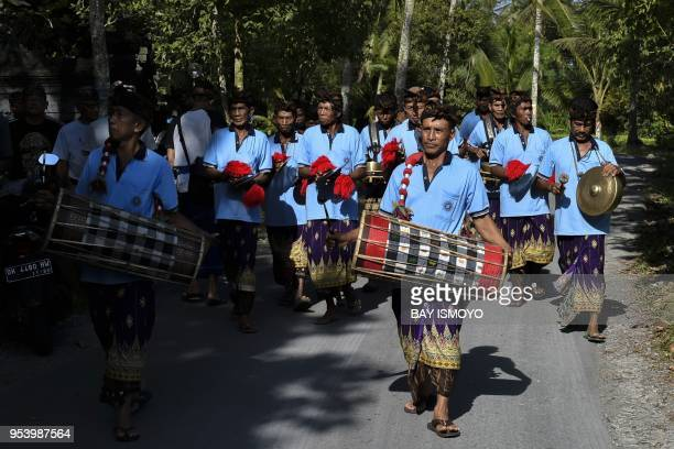 This photo taken on April 18, 2018 shows Balinese musicians performing during a cremation ceremony procession in the village of Buruan Kelod in...