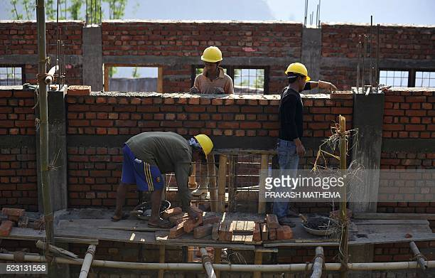 This photo taken on April 19 2016 shows Nepalese workers rebuilding an earthquakedamaged school in Bhuji village in Ramechhap some 100 kilometres...