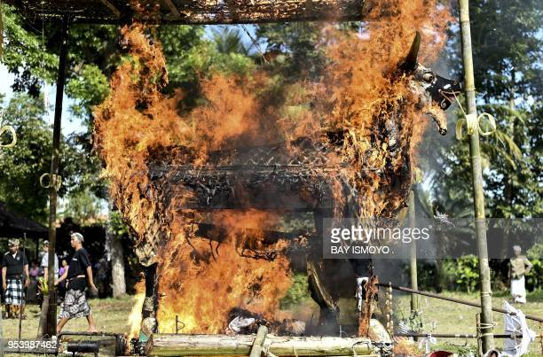 This photo taken on April 19, 2018 shows a large wooden bull with the remains of I Gusti Ketut Tika and Gusti Ayu Made Lemuh burning during a...