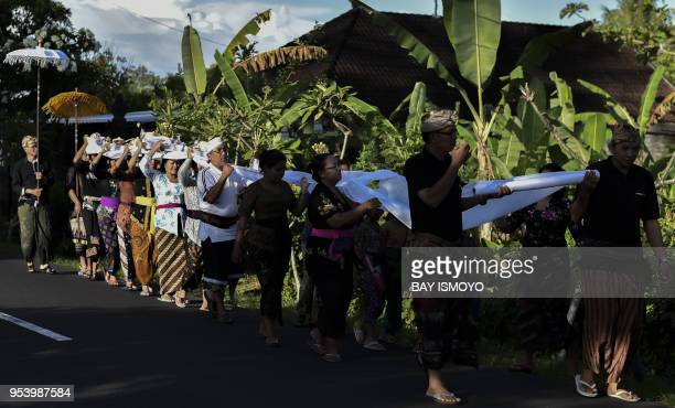 This photo taken on April 19, 2018 shows Balinese family members and villagers walking in a procession as part of a cremation ceremony in the village...