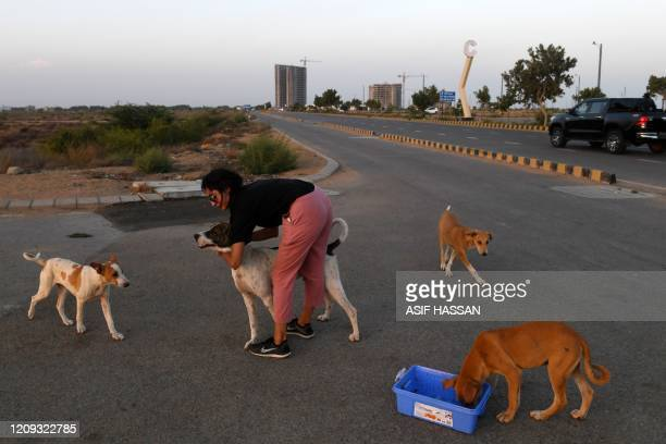This photo taken on April 2, 2020 shows resident Noor Ali feeding stray dogs on a street near Clifton beach during a government-imposed nationwide...