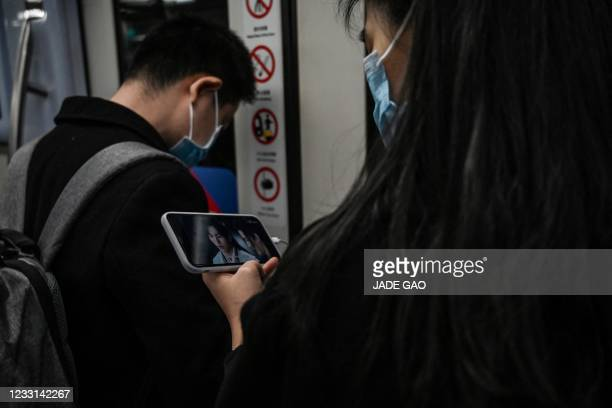 This photo taken on April 2, 2021 shows a woman watching the Chinese television drama 'Word of Honor' on her phone while travelling on the...