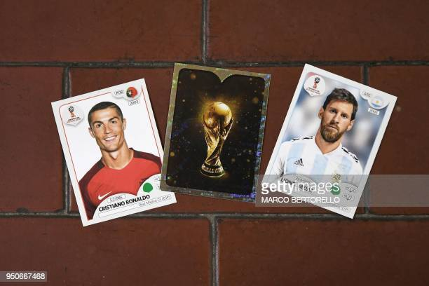 This photo taken on April 20, 2018 shows collectible cards featuring Portugal's forward Cristiano Ronaldo, the Fifa World Cup Trophy and Argentina's...