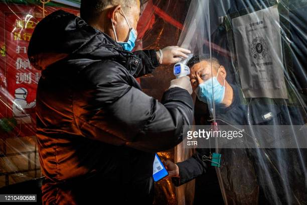 TOPSHOT This photo taken on April 20 2020 shows a staff member checking the body temperature of a resident before he enters a community in Mudanjiang...