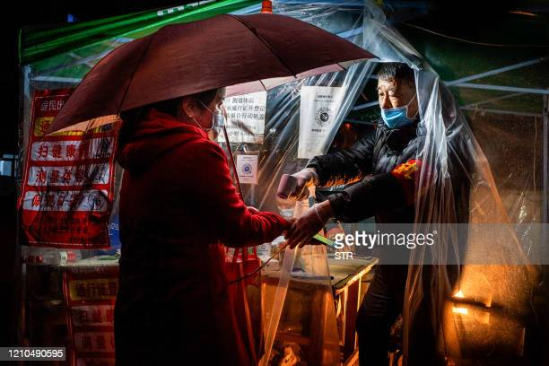 TOPSHOT This photo taken on April 20 2020 shows a staff member checking the body temperature of a resident before she enters a community in...