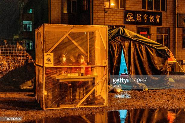 TOPSHOT This photo taken on April 20 2020 shows staff members keeping watch at the entrance of a community in Mudanjiang in China's northeastern...