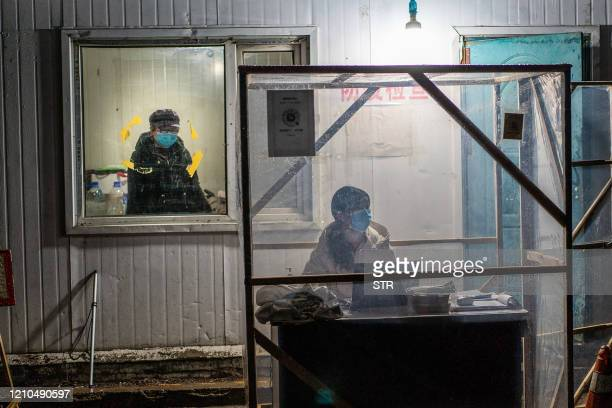This photo taken on April 20 2020 shows staff members keeping watch at the entrance of a community in Mudanjiang in China's northeastern Heilongjiang...