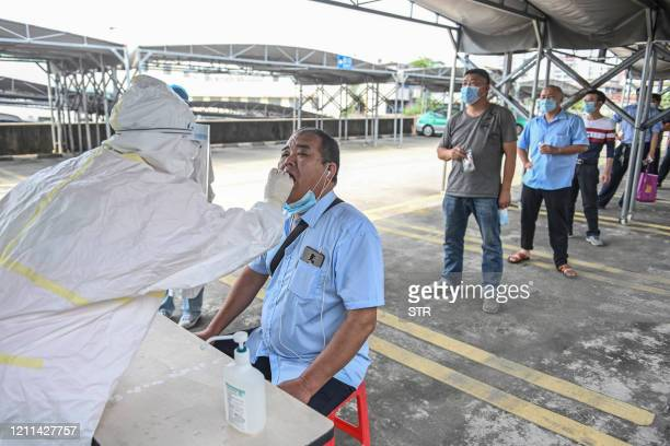 This photo taken on April 20, 2020 shows taxi drivers queueing to receive nucleic acid testing for the COVID-19 coronavirus in Guangzhou in China's...