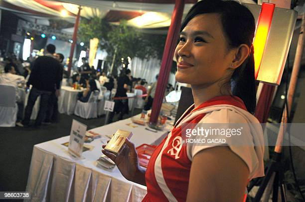 This photo taken on April 21 2010 shows an Indonesian promotion girl displaying cigarettes for sale at a dinner concert sponsored by a local...