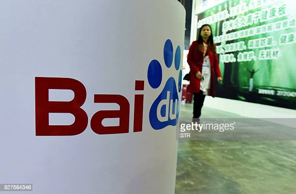 This photo taken on April 21, 2016 shows a woman walking past the Baidu booth at the China International Technology Fair in Shanghai. The head of...