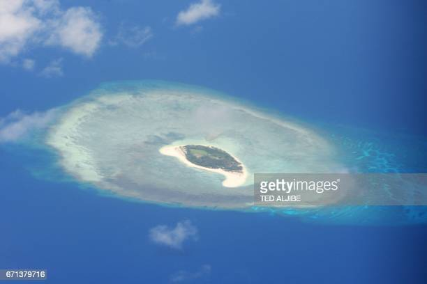 This photo taken on April 21 2017 shows an aerial shot of a reef in the disputed Spratly islands on April 21 2017 Philippine Defence Secretary Delfin...
