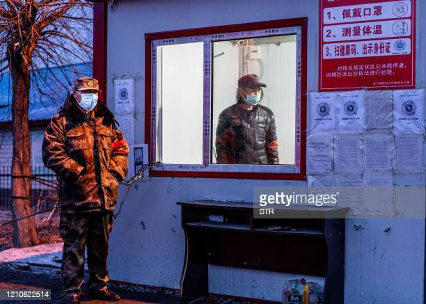 TOPSHOT This photo taken on April 21 2020 shows staff members keeping watch at a checkpoint in the border city of Suifenhe in China's northeastern...