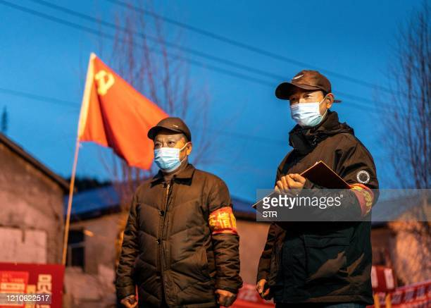 This photo taken on April 21 2020 shows staff members keeping watch at a checkpoint in the border city of Suifenhe in China's northeastern...