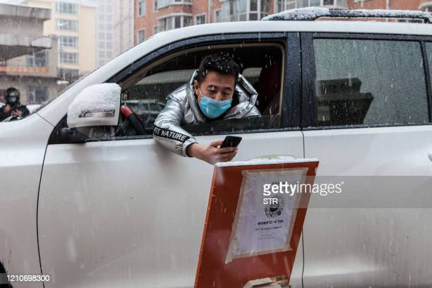 This photo taken on April 22 2020 shows a driver scanning a QR code to register information before entering a community during snowfall in the border...